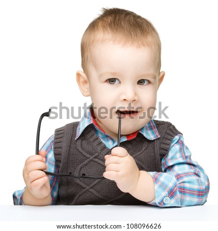 Cute little child play with book and biting glasses while sitting at table, isolated over white