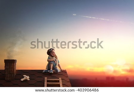 Cute little child playing on the roof of the house and looking at the sky and dreaming of becoming a pilots. - stock photo