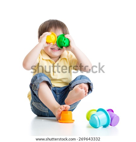 Cute little child playing with toys while sitting on floor, isolated over white - stock photo