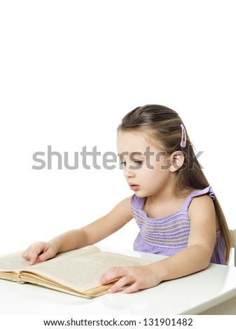 cute little child reading book sitting behind a table at home with copy space for your text