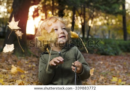 Cute little child with blonde curly hair enjoying in the park in autumn at sunset, watching falling leaves