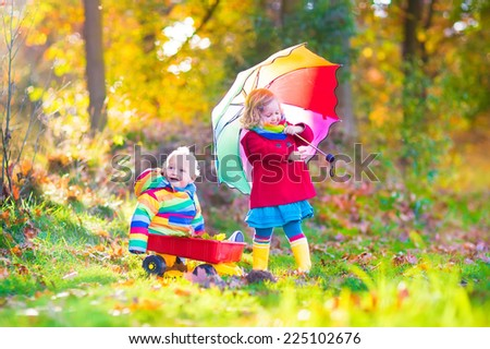 Cute little children, adorable toddler girl and a funny baby boy, brother and sister, playing in a sunny autumn park with a wheel barrow and colorful umbrella - stock photo