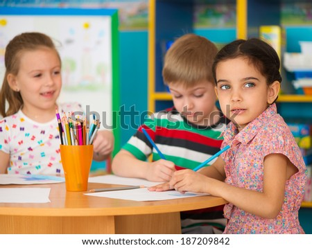 Cute little children drawing and studying at daycare - stock photo