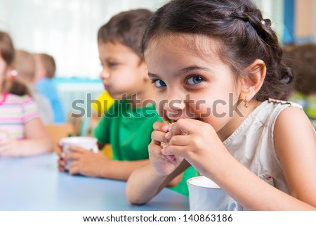 Cute little children drinking milk at daycare - stock photo