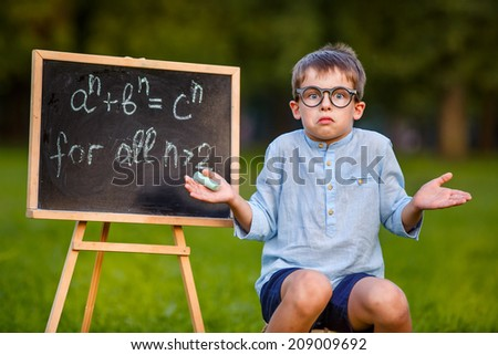 Cute little confused student - stock photo