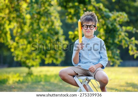 Cute little confused student sitting in garden on beautiful spring day - stock photo