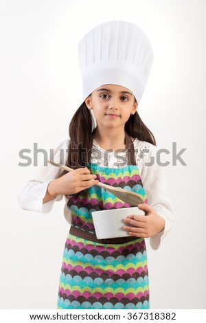 Cute little cook or chef in a colorful apron and toque standing holding a basin and wooden spoon as she does the baking, isolated on white - stock photo