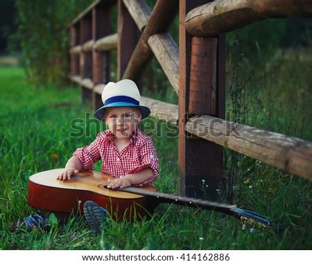 cute little cowboy playing guitar - stock photo