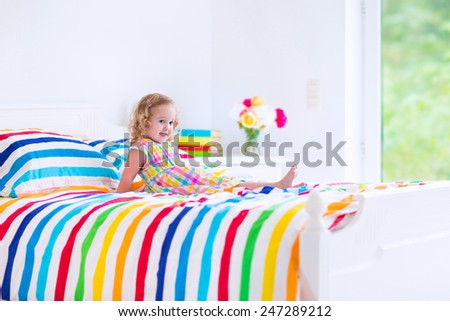 Cute little curly toddler girl in a colorful dress jumping on a big white bed laughing and having fun on a sunny weekend morning in a bedroom - stock photo