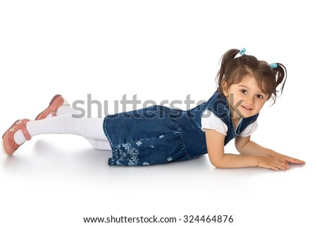 Cute little dark-haired girl with short pigtails on her head lying on the floor. Girl wearing a blue dress and white tights-Isolated on white background - stock photo