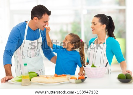 cute little daughter feeding father a piece of tomato in kitchen - stock photo
