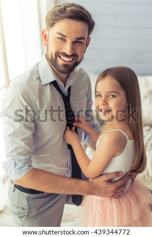 Cute little daughter is adjusting her father's tie. Both are looking at camera and smiling