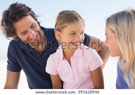 Cute little daughter looking at mother with a smile. Family enjoying holiday at beach. Little girl in conversation with her parents outdoor. - stock photo