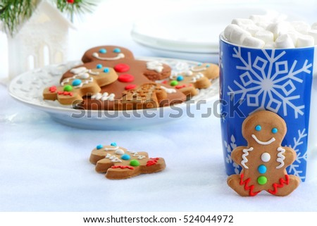 Cute little decorated gingerbread men with snowflake mug of hot chocolate and mini marshmallows for a Christmas treat