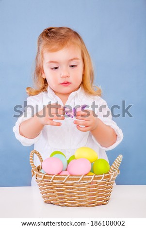 cute little easter girl with eggs - stock photo