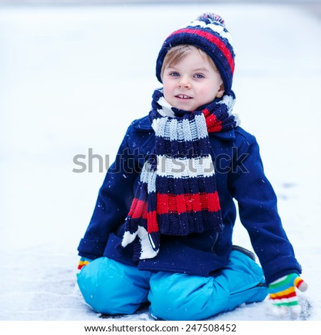 Cute little funny boy in colorful winter clothes having fun with snow, outdoors during snowfall. Active outdoors leisure with children in winter. Kid with warm hat, hand gloves and scarf  - stock photo