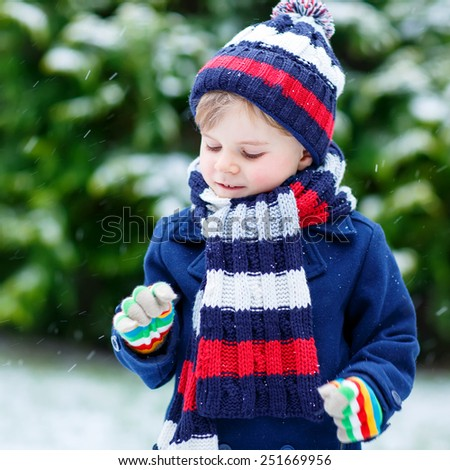 Cute little funny child in colorful winter clothes having fun with snow, outdoors during snowfall on cold day. Active outoors leisure with children in winter. - stock photo