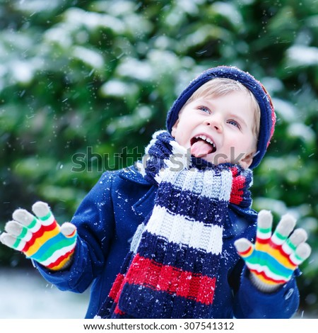 Cute little funny child in colorful winter clothes having fun with snow, outdoors during snowfall. Active outdoors leisure with children in winter. Kid with  hat, hand gloves with stripes. - stock photo