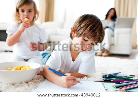 Cute little gir eating chips and her brother drawing in the living-room - stock photo
