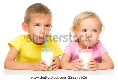 Cute little girl and boy are drinking milk using straw, isolated over white - stock photo