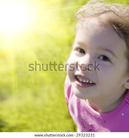 Cute little girl and bright summer sun - stock photo