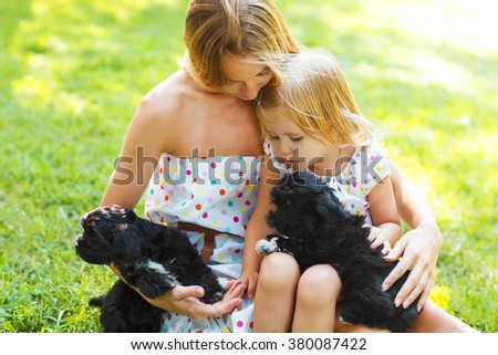 Cute little girl and her mother hugging dog puppies. Friendship and care concept - stock photo