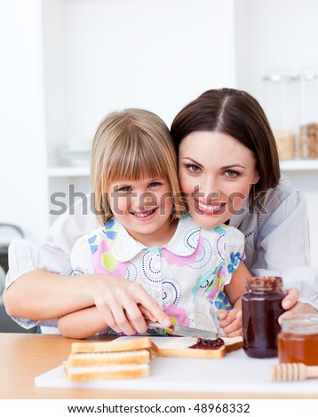 Cute little girl and her mother preparing toasts in the kitchen