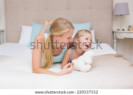 Cute little girl and mother on bed at home in the bedroom - stock photo