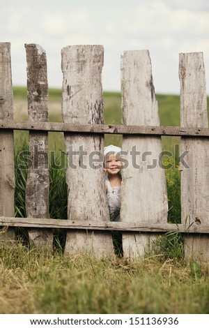 cute little girl and wooden fence - stock photo