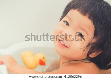 cute little girl bathing with a yellow duck in the bathroom.Morning light tone. - stock photo