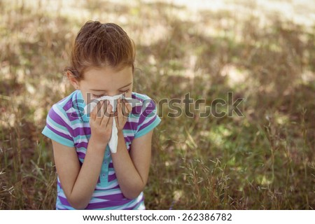 Cute little girl blowing her nose in park on a sunny day - stock photo