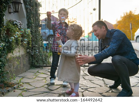 Cute little girl blowing soap bubbles outdoors - stock photo
