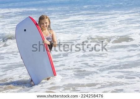 Cute little girl boogie boarding in the ocean - stock photo