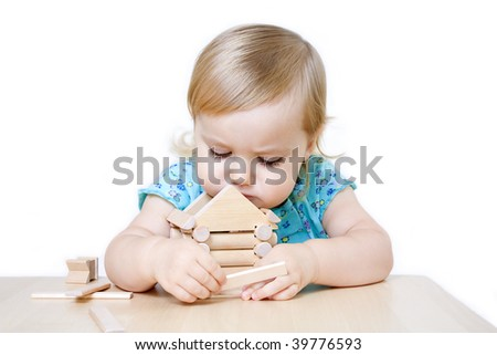 Cute little girl building toy house