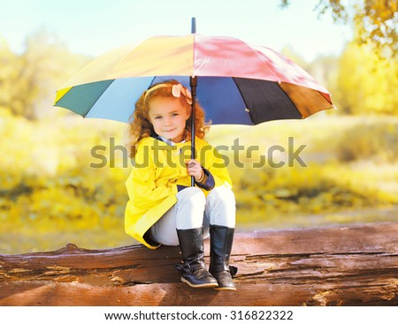 Cute little girl child with colorful umbrella in sunny autumn park - stock photo