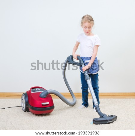 Cute little girl cleaning carpet with vacuum cleaner. - stock photo