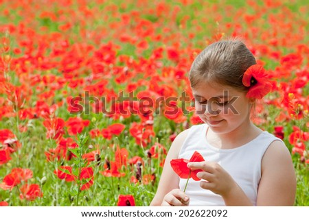 Cute little girl closeup portrait, collecting poppies on meadow and with flower in her hair - stock photo