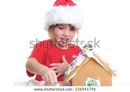 Cute Little Girl Decorating a Gingerbread House on a White Background for Christmas - stock photo