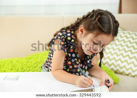 Cute little girl doing her homework, close-up, on home interior background - stock photo