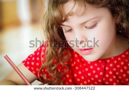 Cute little girl doing her homework coloring - stock photo