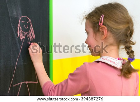 Cute little girl drawing a picture on blackboard. - stock photo