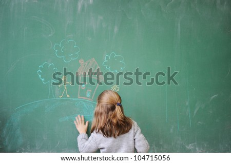 Cute little girl drawing on blackboard - stock photo