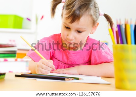Cute little girl drawing with colorful pencils at home