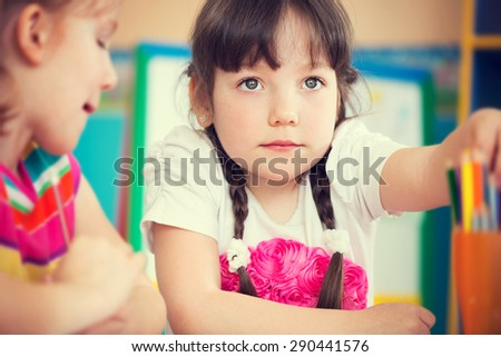 Cute little girl drawing with colorful pencils at kindergarten - stock photo