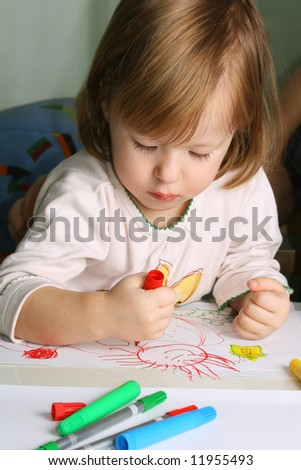 Cute little girl drawing with markers