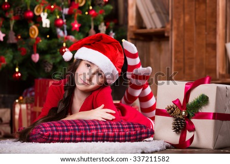 Cute little girl dreaming near the Christmas tree. Happy new year. Waiting for Santa. - stock photo