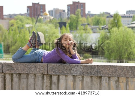 Cute little girl dressed in jeans lying on a high stone parapet and dreaming with closed eyes over city background - stock photo