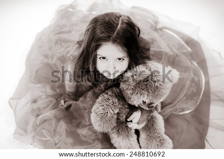 Cute little girl dressed like princess with her teddy-bear toy friend - stock photo