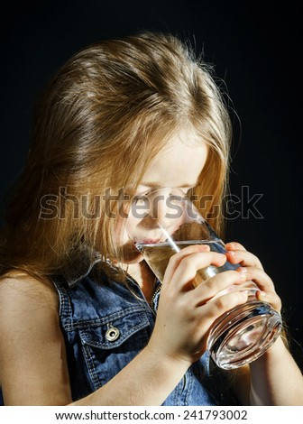 Cute little girl drinking clear water from glass