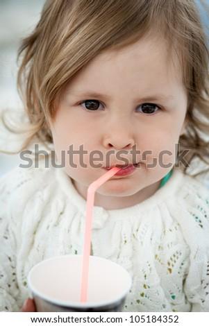 Cute little girl drinking milk using drinking straw - stock photo
